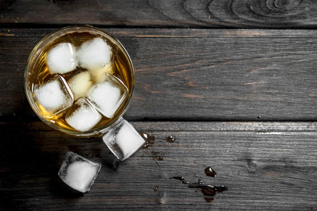 Whiskey in a glass with ice cubes. On wooden background