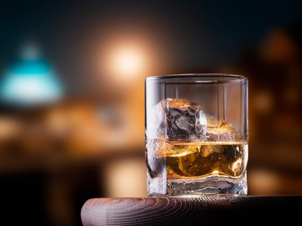 Glass of whiskey with ice cubes on the wooden table with city view background