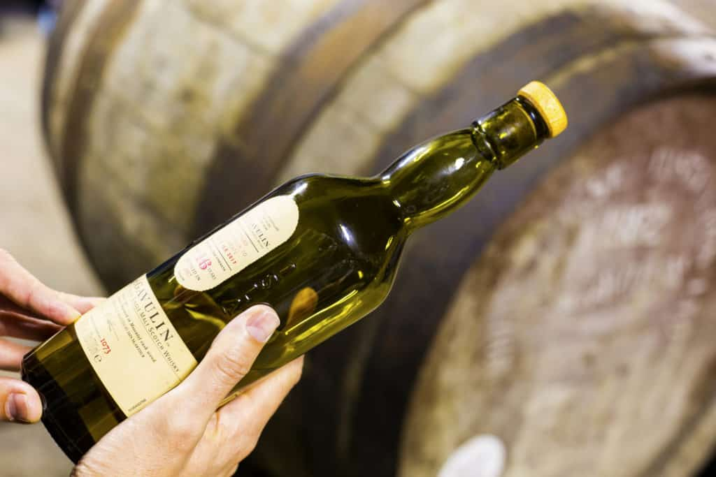 Someone holds a bottle of 16 years aged Lagavulin single malt whisky at the Lagavulin whisky distillery with old oak cask on the background.