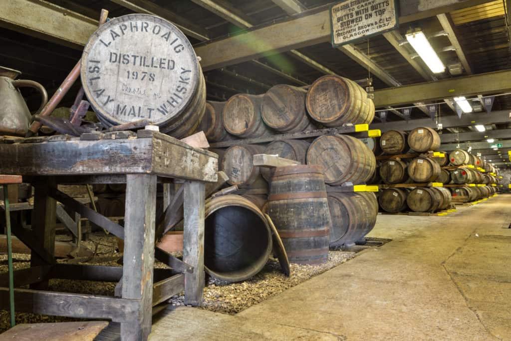 Old wooden barrels and casks at Lafroaig whisky distillery warehouse established in 1815.