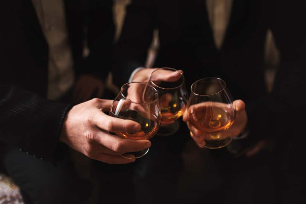 men with a friend. hold in the hands of glasses of whiskey. close up