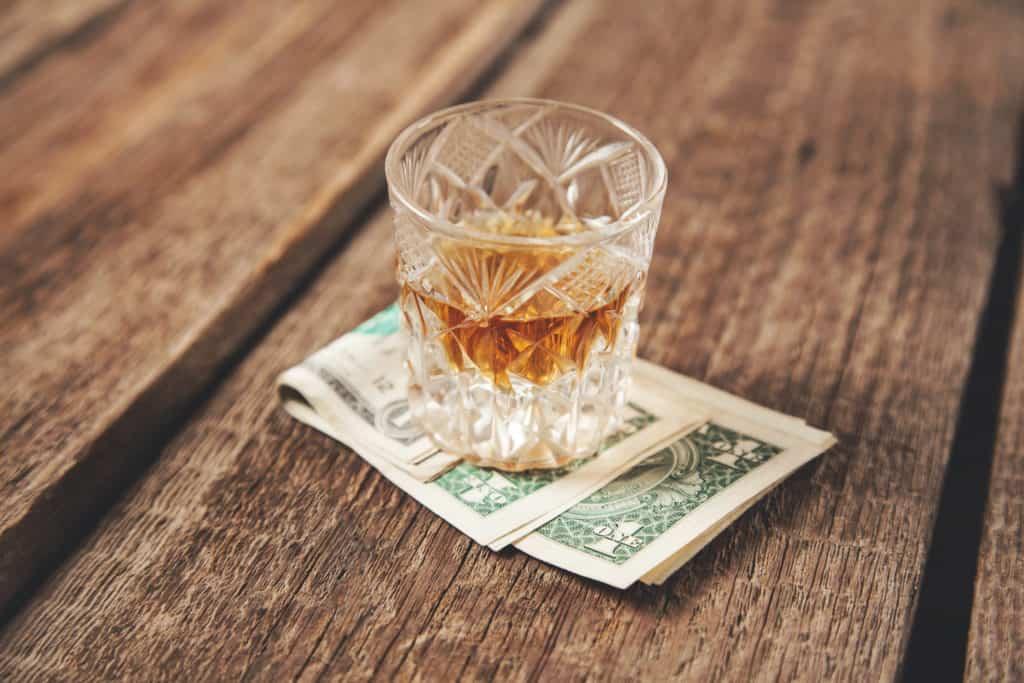 whiskey glass on money onthe wooden desk