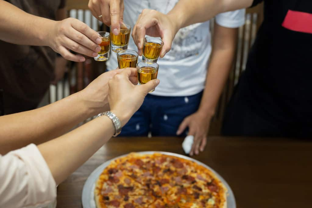 Friend with rum shots on party with pizza on table