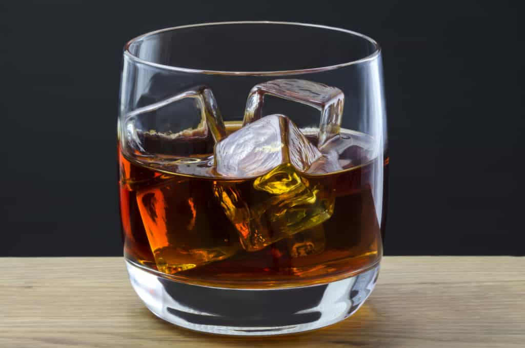 A large whiskey poured over ice cubes in a plain glass