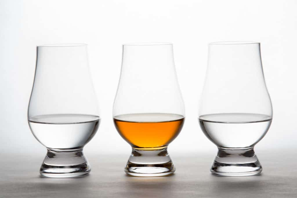 Three backlit crystal glasses containing clear and amber liquor.  Vodka, whiskey, bourbon, brandy, etc.