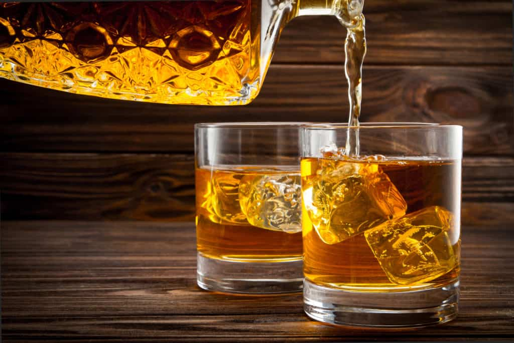 Pouring whiskey from bottle in the glasses on wooden background
