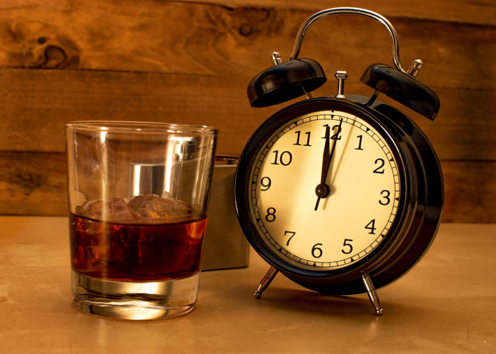 Alcoholism concept. Glass tumbler with whiskey and ice next to a black clock.