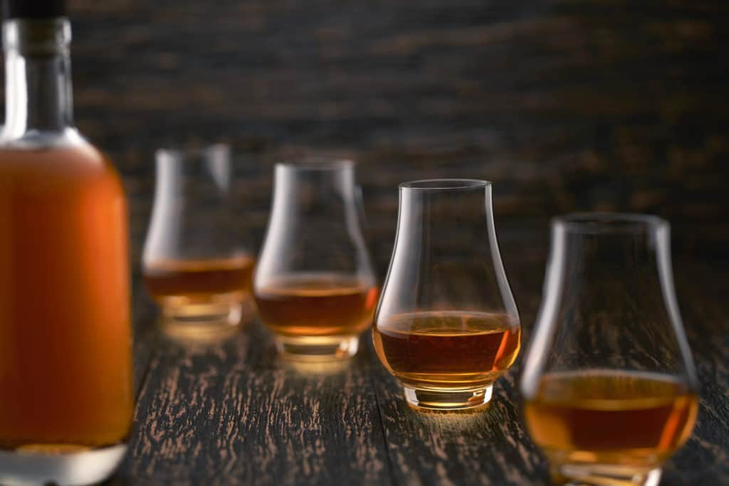 glasses of single malt whiskey on a wooden table with the silhouette of a bottle of whiskey.